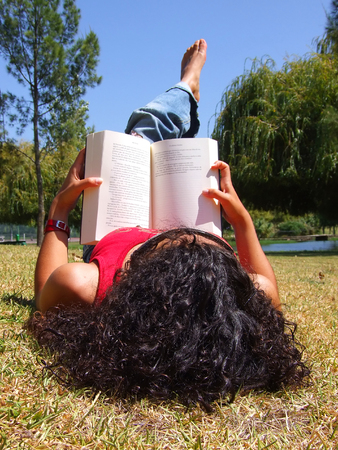 young girl reading book in park