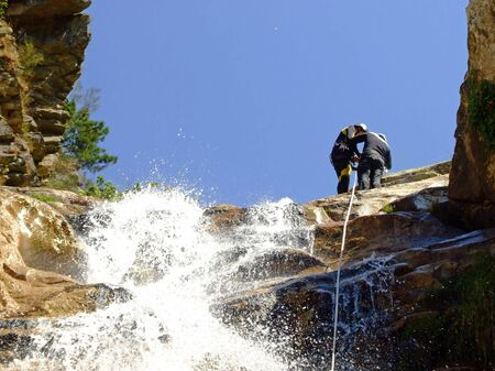 Couple prepering to descende a waterfall with roupes