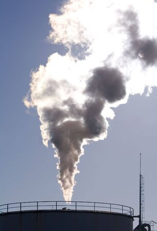 blocking: Industrial plant exhausting smokes into the atmosphere blocking the sun. Stock Photo