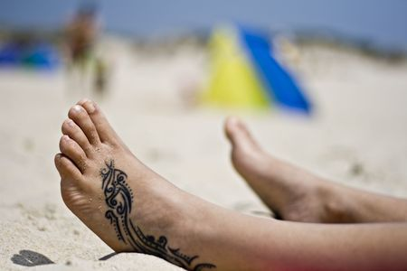 hollidays: Woman foot with a tattoo in the sand