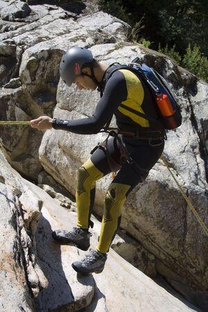 Men descending waterfall in rappel photo