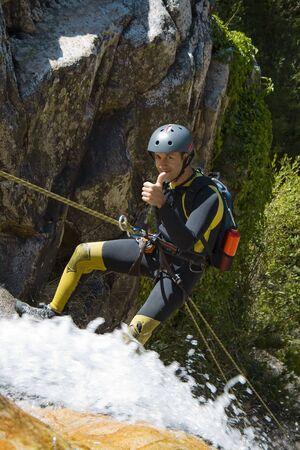 descending: Men descending waterfall in rappel Stock Photo