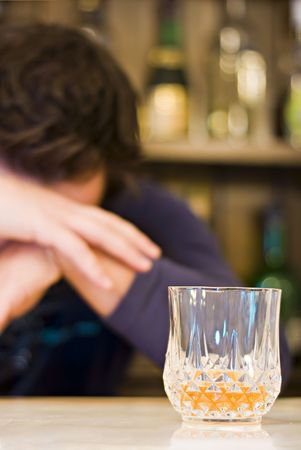forground: Men depressing with a drink in the forground