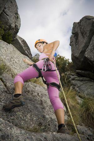 Youn woman descending in rappel with attitude