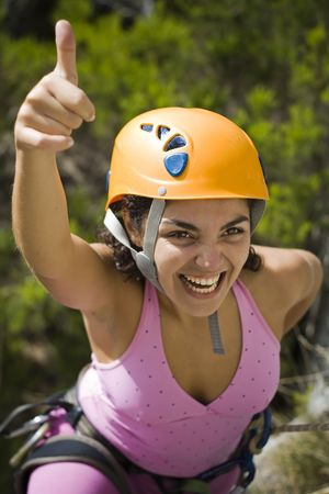 recreational climbing: Woman with the hand up happy by the sucess rapel