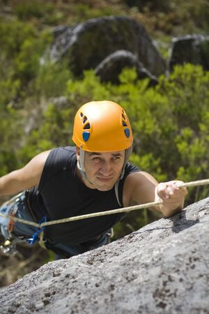 outdoor pursuit: Man climbing a mountain with a protetive helmet