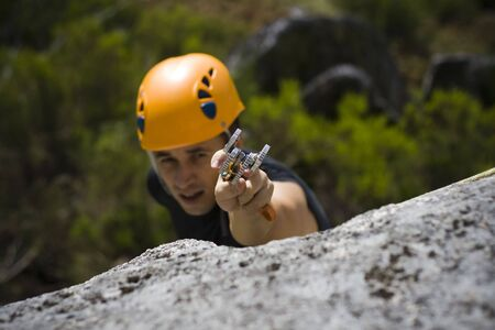 outdoor pursuit: Man climbing a mountain with a camming device in his hand Stock Photo
