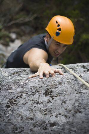 Man climbing a mountain with a protetive helmet Stock Photo - 5813389