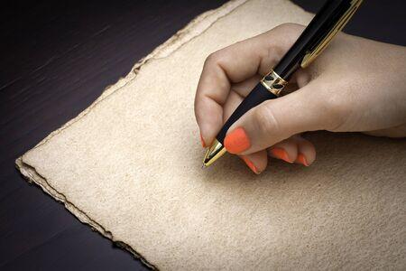 pad pen: Mujer a punto de escribir en un papel de caf� negro de reciclaje Foto de archivo
