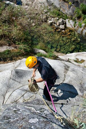 Men prepering to rappeling on waterfall photo