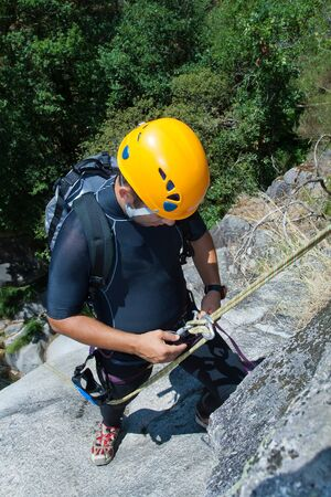 rappeling: Men prepering to rappeling on waterfall checking is safe line and securety