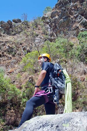 rappeling: Men staring into horizont and prepering to rappeling into a canyon