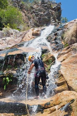 rappeling: Men descending in rappeling a waterfall