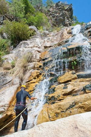 rappelling: Youn men descending waterfall in rappelling