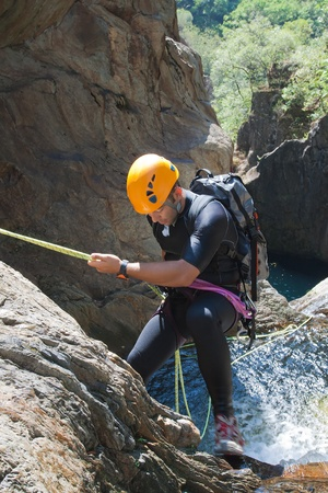 extreme sports: Men descending in rappeling a waterfall