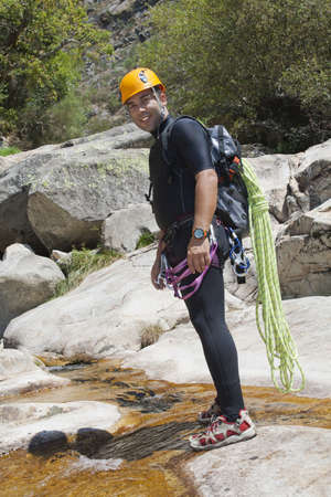 pratice: Men in a river in a canyon equiped to pratice canyoning