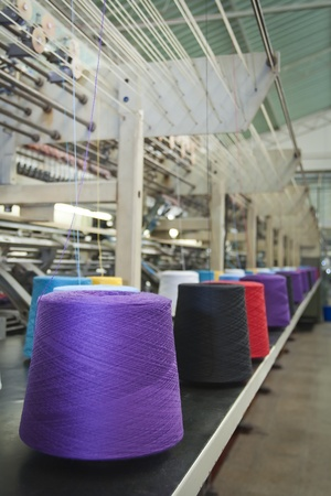 polyester: Textile machine weaving with cone fiber with several colors Editorial