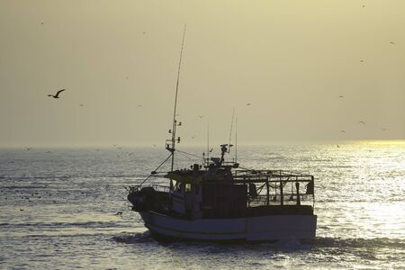 commercial fishing net: Fishing boat on the sunset departerd for a new day