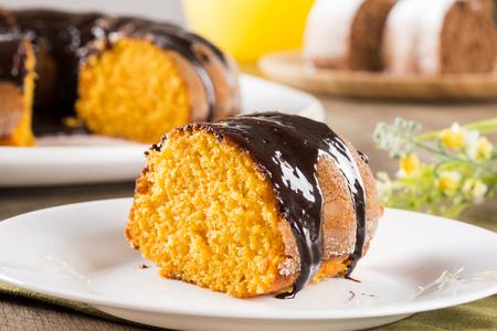 marchewka: Ciasto marchewkowe z czekoladą i plasterek na stole.