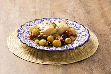 codfish: A typical Portuguese dish with codfish called Bacalhau do Porto in a original portuguese plate. Cod Fish Prepared. Stock Photo