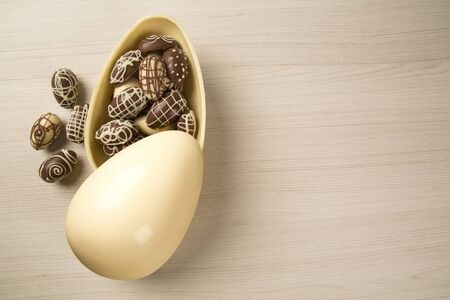 Chocolate Easter Eggs Over Wooden Background. Easter Egges desserts.