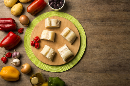 codfish: salted codfish on the wooden table with ingredients. Cod Fish Raw. Stock Photo