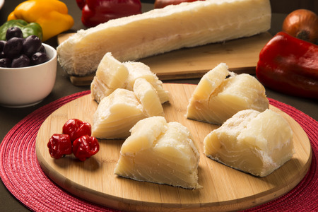 whitefish: salted codfish on the wooden table with ingredients. Cod Fish Raw. Stock Photo