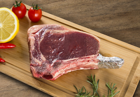 prime: Raw meat selection on wooden cutting board. Prime ribe. Stock Photo