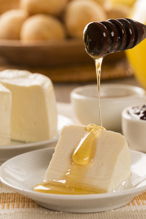 different types of cheese: Brazilian sheep cheese. Bread, Fruits and different types of cheese in the background.