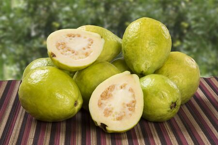 alf: white guava cut in a alf in over some entire white guavas over a striped surface on a plantation background.