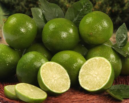 Fresh citrus lime with mint close up on wooden background. Fresh fruits.