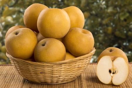 Algunos peras asiáticas más de una superficie de madera. Frutas frescas Foto de archivo