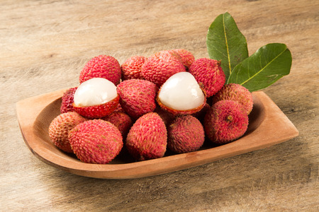 lychees: fresh lychees on wooden surface. Fresh fruits