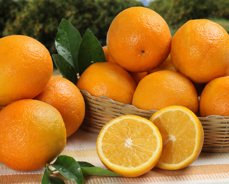 Close up of some oranges in a basket over a wooden surface. Fresh fruit.