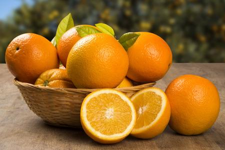 naranja: Cierre de algunas naranjas en una cesta sobre una superficie de madera. Fruta fresca.