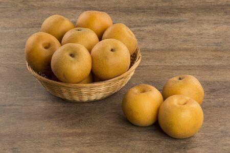 Algunos peras asiáticas más de una superficie de madera. Foto de archivo