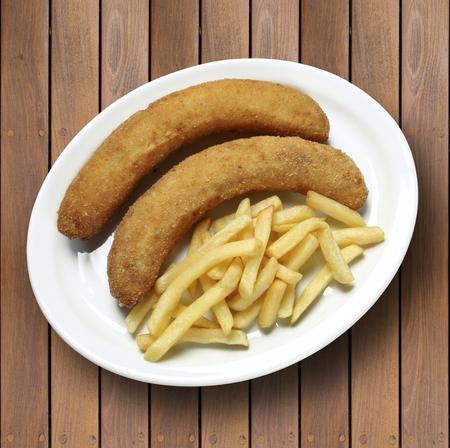 platanos fritos: hot fried bananas in plate with fried potato. Foto de archivo