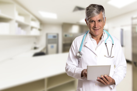 patient notes: Doctor checking patient notes on a tablet-pc standing with his stethoscope around his neck reading the information on the screen. Stock Photo