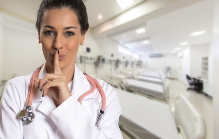 Serious doctor woman making silence sign over hospital.
