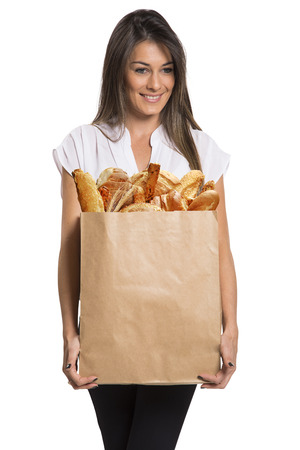 bolsa de pan: Smiling woman holding a grocery bag with bread in white background. Foto de archivo