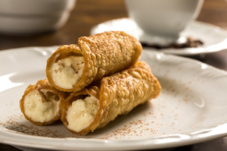 typical Sicilian pastries called CANNOLI with amarena listed in pastry on the plate. Stock Photo