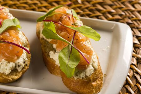 cress: Bruschetta with chopped mango, cress and goat cheese on fresh baguette on the table.