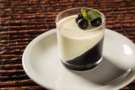 Italian dessert pannacotta with redfruit and mint on wooden background. Stock Photo