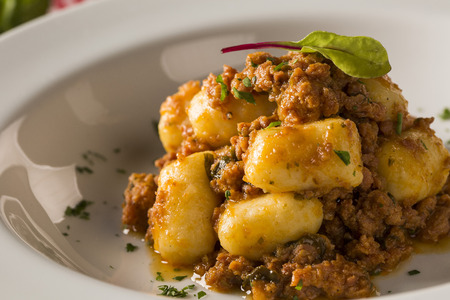 Portion of gnocchi in tomato sauce with cheese. Stock Photo