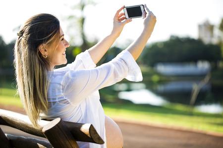 hands free phone: Pregnant woman making self portrait using smartphone.