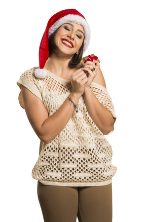 envisioning: Christmas gift. Smiling beautiful woman in red hat and scarf envisioning with closed eyes what is in the gift box, in white background. Stock Photo