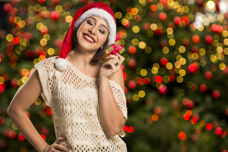 envisioning: Christmas gift. Smiling beautiful woman in red hat and scarf envisioning with closed eyes what is in the gift box, over christmas background