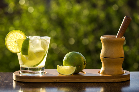 caipirinha: Lemon Fruit Caipirinha of Brazil on green blurry background Stock Photo
