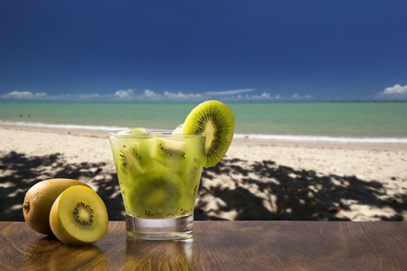 caipirinha: Kiwi Fruit Caipirinha of Brazil over beautiful beach background
