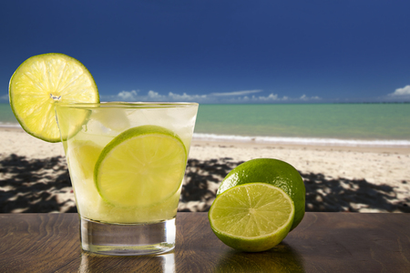 caipirinha: Lemon Fruit Caipirinha of Brazil over beautiful beach background